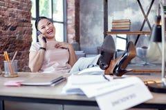 Glad kvinnlig anställd som skvallrar på telefonen arkivfoton