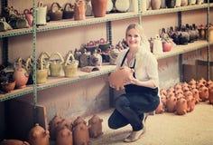 Glad kvinnlig hantverkare som har keramik i seminarium Royaltyfri Foto