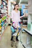 Glad kvinnlig kund som väljer apotekprodukter Fotografering för Bildbyråer