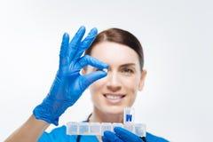 Glad kvinnlig labbassistent som tar preventivpillerar från behållaren royaltyfri foto