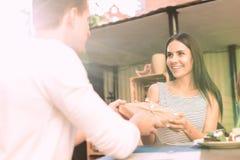 Glad långhårig flicka som accepterar den angenäma gåvan från hennes man arkivbilder