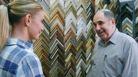 Glad le arbetare för hög man som pratar med kunden om ramar i atelier Fotografering för Bildbyråer