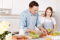 Glad le fadermatlagning med hans dotter arkivfoto