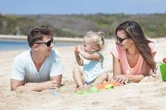 Glad liten familj som ligger på sand på stranden Royaltyfria Foton