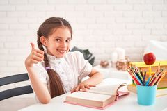Glad liten flicka som sitter på tabellen med blyertspennor och läroböcker Lycklig barnelev som gör läxa på tabellen h?rligt royaltyfri fotografi