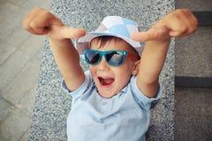 Glad liten pojke i solglasögon som ger upp två tummar, medan ligga Arkivfoto