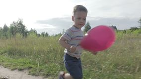 A little boy with a balloon. Glad, little boy in shorts and a t-shirt running on the lawn with a pink balloon stock video