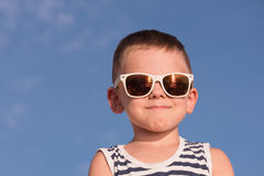 Glad little boy wearing sunglasses on blue sky background Royalty Free Stock Images