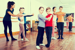 Glad little boys and girls dancing pair dance Stock Photos