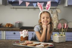 Glad little lady preparing for celebration. Portrait of beautiful young girl in country style kitchen sitting at table with easter cake, cookies and basket with Stock Images