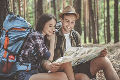 Inspired tourists preparing for journey. Glad loving couple is sitting and reading a map in forest. Woman is hugging men with smile Royalty Free Stock Photos