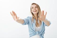Glad lycklig caucasian flickvän med ganska hår som drar händer in mot kamera som, om gå i mörker som i huvudsak ler Arkivfoton