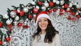 Glad lycklig flicka i den röda santa hatten att överföra en kyss som ser kameran i jul dekorerad studio arkivfilmer