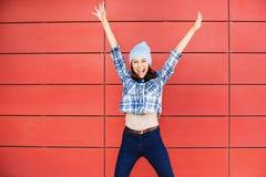 Glad lycklig ung kvinna som hoppar mot den röda väggen Upphetsad härlig flickastående fotografering för bildbyråer