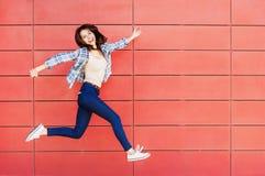 Glad lycklig ung kvinna som hoppar mot den r?da v?ggen Upphetsad h?rlig flickast?ende arkivbild