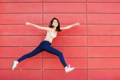 Glad lycklig ung kvinna som hoppar mot den r?da v?ggen Upphetsad h?rlig flickast?ende royaltyfria foton