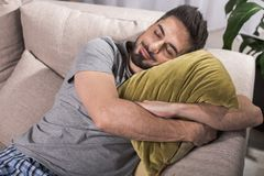Glad male dreaming in living room. Nice and cozy. Top view of satisfied young man lying and embracing pillow while having nap on sofa Royalty Free Stock Photography