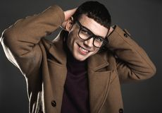 Glad male looking at camera. Portrait of outgoing young man putting hands behind head. He isolated on black background. Cheerfulness concept Royalty Free Stock Photo
