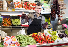 Glad male seller showing assortment of grocery shop Stock Photography
