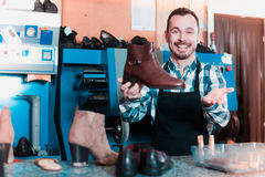 Glad male worker showing fixed shoes. In shoe repair workshop Royalty Free Stock Image