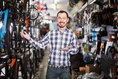 Glad man in bicycle shop chooses for himself sports bike Royalty Free Stock Image
