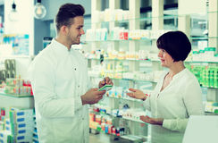 Glad man druggist in white coat. Cheerful adult men druggist in white coat giving advice to customers in pharmacy Royalty Free Stock Image