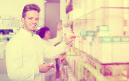 Glad man druggist in white coat. Portrait of cheerful men druggist in white coat giving advice to customers in pharmacy Royalty Free Stock Photography