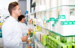 Glad man druggist in white coat. Portrait of glad men druggist in white coat giving advice to customers in pharmacy Stock Photos