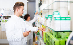 Glad man druggist in white coat. Portrait of smiling men druggist in white coat giving advice to customers in pharmacy Stock Photography
