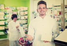 Glad man druggist in white coat. Positive men druggist in white coat giving advice to customers in pharmacy Royalty Free Stock Image