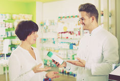 Glad man druggist in white coat. Smiling adult men druggist in white coat giving advice to customers in pharmacy Stock Photos