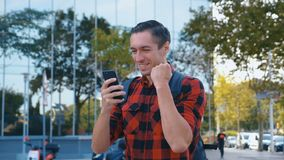 Glad man firar en sportvadslagningsfest på en mobil telefon i stan i Modern Glass-byggnad lager videofilmer