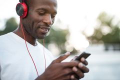 Glad man hearing song on open air. Outgoing male listening music in headsets while sending message by mobile outdoor Stock Images