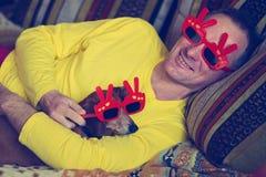 Glad man och en rolig liten hund, i karnevalsolglasögon Arkivfoto