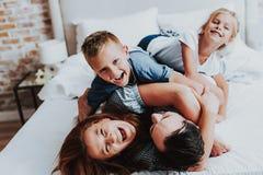 Glad man och kvinna som har gyckel med ungar royaltyfria foton