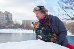 Glad man och liten hund som bär i roliga hattar för en vinter Arkivbilder