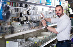 Glad man picking electric plug in household shop Stock Image