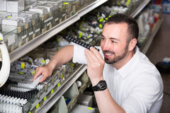 Glad man picking electric plug in household shop Royalty Free Stock Photo