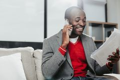 Satisfied businessman using gadget and looking at documents. Glad man resting on sofa at home with papers in hand. He is communicating by cellphone with delight Royalty Free Stock Photos