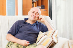 Glad man sitting on a couch royalty free stock photo