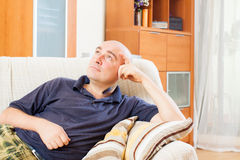 Glad man sitting on a couch stock photo
