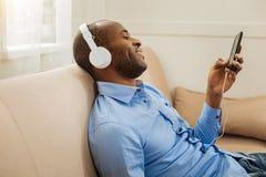 Glad man som lyssnar till musik och att koppla av Arkivfoto