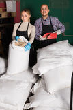 Glad man and woman holding gunnysacks with malt Royalty Free Stock Photos