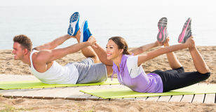 Glad man and woman training on beach by sea Stock Image