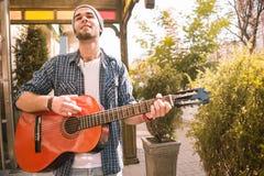 Glad manlig gitarrist som gör perfekt expertis på gatan royaltyfri fotografi