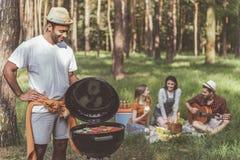 Glad manmatlagninggrillfest för vänner i skog royaltyfri foto