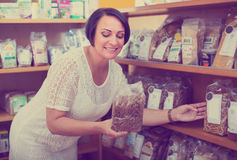 Glad mature female customer holding with cereal Stock Photo