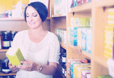 Glad mature female customer holding dietary supplements Royalty Free Stock Photos