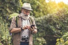 Glad mature male tourist using smartphone Royalty Free Stock Photo