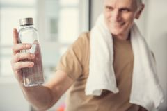 Glad mature man showing refreshing beverage. Smiling pensioner standing with towel on his neck. Focus on bottle of water he is holding in hand Royalty Free Stock Photography